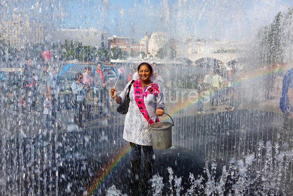 Thames Festival 08, <br /> During the summer months, outside the newly refurbished Royal Festival Hall a young woman on her hen party plays in rooms created by walls of water.<br /> <br /> Danish artist Jeppe Hein's aquatic sculpture Appearing Rooms was originally commissioned for the garden of the Villa Manin, Italy. Inspired by the Baroque villa, he designed an ornamental fountain that combines sculpture, architecture, and technology and playfully invites visitors to interact with the changing spaces created by rising and falling walls of water.