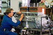 Engineer working on car engine of vintage car being restored at Ashton Keynes Vintage Restorations in Wiltshire, UK