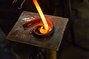 Blacksmith Frank Verga using a form to shape hot iron in an metal shop in Charleston, SC