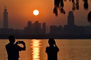 Two people taking a picture of the Sunset skyline of Wuhan, East Lake Greenway park, Wuhan, Hubei, China