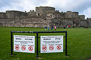 An English / Welsh bilingual sign in front of Beaumaris Castle, the greatest castle never built, on 17th of February 2020 in Beaumaris, Anglesey, Wales, United Kingdom. Beaumaris castle was a fortress built as part of Edward I's campaign to conquer north Wales after 1282. It is a symmetrical masterpiece that was never quite finished.