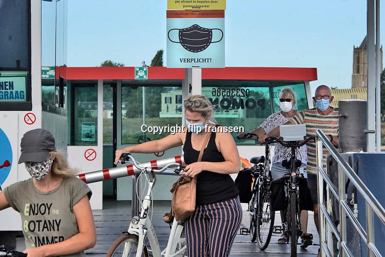 Nederland, Tiel, Wamel, 21-8-2020 Passagiers op het fietspontje van Tiel naar Wamel in het land van maas en waal . Ze dragen verplicht een mondkapje vanwege het coronabesmettingsgevaar .Foto: ANP/ Hollandse Hoogte/ Flip Franssen