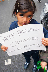 Kesnington, London, July 11th 2014. A little girl adds her message as thousands of Palestinians and their supporters demonstrate against the latest wave of Israeli retaliatory attacks on Palestinian targets and homes, where casualties are steadily mounting.