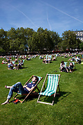 People lying on the grass and sitting on deck chairs in the sun at Green Park, central London. This park, near to Buckingham Palace is one of the Royal Parks and is a huge draw for tourists and locals alike.