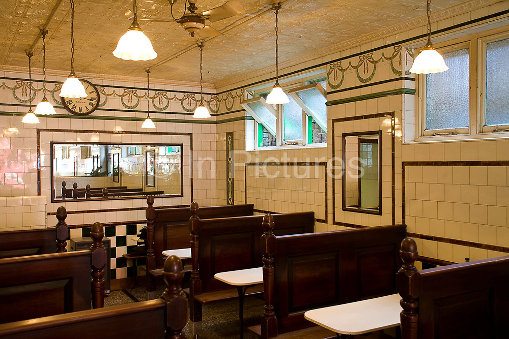 The interior (including the painted tin tiles on the ceiling) of Manze's Eel, Pie and Mash shop in Walthamstow, East London, UK.Although the shop still trades under the original Manze name, it is now independently owned and no longer part of the Manze family. This resturant is a Grade-2 listed building with antique pressed-tin tiles on the ceiling.Eel, pie and mash shops are a traditional but dying business. Changing tastes and the scarcity of the eel has meant that the number of shops selling this traditional working class food has declined to just a handful mostly in east London. The shops were originally owned by one or two families with the earliest recorded, Manze's on Tower Bridge Road being the oldest surviving dating from 1908. Generally eels are sold cold and jellied and the meat pie and mash potato covered in a green sauce called liquor.