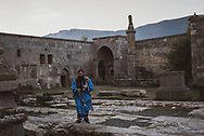 At sunrise, an Armenian priest doing liturgical censing with a thurible walks on the grounds of Tatev monastery in Armenia. (October 1, 2016)