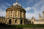 "As a wide general view, we see the famous Oxford landmark, the Radcliffe Camera without people but with a solitary modern bicycle chained to railings of this circular 16th century construction. The round building is in afternoon sunshine is foreground and the walls and towers of All Souls College is seen behind with its gold gates just above the bike. The Radcliffe Camera (colloquially, ""Rad Cam""; ""Radder"" in 1930s slang) is a building in Oxford, England, designed by James Gibbs in the English Palladian style and built in 1737–1749 to house Oxford University's Radcliffe Science Library (source Wiki). Radcliffe Camera rises 150 feet (46 meters) above cobbled Radcliffe Square."