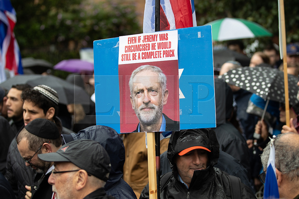 """© Licensed to London News Pictures . 16/09/2018. Manchester, UK. A placard reading """" Even if Jeremy was circumcised he would still be a complete prick """" with a photograph of Labour leader Jeremy Corbyn . Thousands of people including the UK's Chief Rabbi and several Members of Parliament attend a demonstration against rising anti-Semitism in British politics and society , at Cathedral Gardens in Manchester City Centre . Photo credit : Joel Goodman/LNP"""
