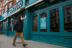 © Licensed to London News Pictures. 06/03/2021. London, UK. A man walks past closed businesses in north London. Businesses of any size in England will be able to sign up to receive free rapid Covid-19 tests, as announced by the government under its workplace testing programme. The Covid-19 lockdown roadmap will begin from Monday 8 March, as primary and secondary schools reopen in England. Photo credit: Dinendra Haria/LNP