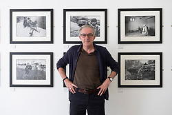 Craig Wallace editor of Sogo Arts magazine in the Sogo Arts gallery on Saltmarket in Glasgow, Scotland, UK. War photography exhibition by David Pratt current exhibition.