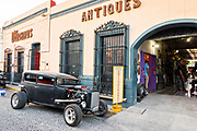 An old hot rod style automobile outside an antique shop in the Barrio Antiguo or Spanish Quarter neighborhood adjacent to the Macroplaza Grand Plaza in Monterrey, Nuevo Leon, Mexico.