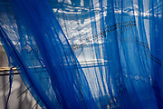 Blue safety netting from a Westminster construction site, blows in the breeze in central London. Hanging from a point at the top of the building, we see the texture of the netting material, its holes and folds, creases and close stitching that screens off the work being carried out behind on site. Light shines across the blue hues making the industrial place look artistic and with a modernist beauty.