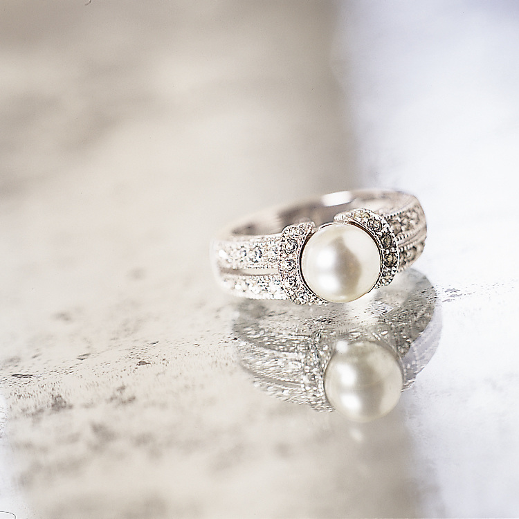 Photograph of a pearl ring shot on a mirror. This peace of jewelry was shot on an antique mirror.