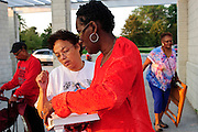Avis Coleman (in red) and Vanessa Molina (in white) decide which hymns to sing for a sunrise mass at Rainbow Beach on the city's south side to pray for peace and non-violence during the upcoming school year. The event hosted by The Black Catholic Deacons in the Archdiocese of Chicago is one of six simultaneous masses along Chicago's lakefront. August 25, 2012 l Brian J. Morowczynski~ViaPhotos...For use in a single edition of Catholic New World Publications, Archdiocese of Chicago. Further use and/or distribution may be negotiated separately. Contact ViaPhotos at 708-602-0449 or email brian@viaphotos.com.