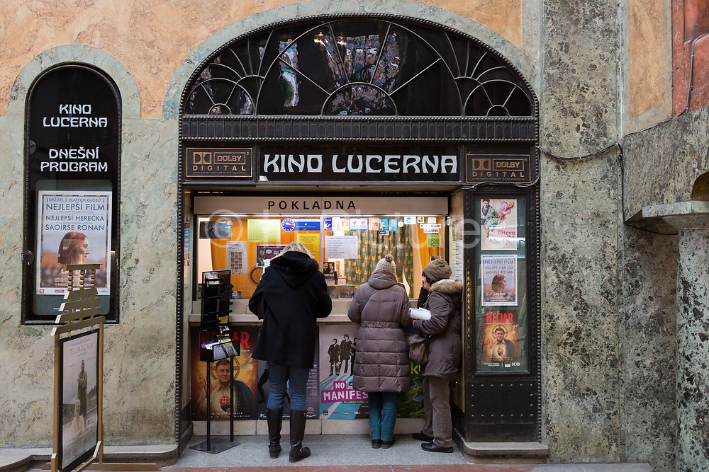 Cinema-goers buy tickets for Kino Lucerna in the marbled atrium kiosk in Lucerna Gallery, on 19th March, 2018, in Prague, the Czech Republic. Lucerna is the most elegant of Nove Mesto's many shopping arcades runs through the art-nouveau Lucerna Palace 1920, between Stepanska and Vodickova streets. The complex was designed by Vaclav Havel grandfather of the former president, and is still partially owned by the family. It includes theatres, a cinema, shops, a rock club and several cafes and restaurants. Here St Wenceslas sits astride a horse that is decidedly dead; it's safe to assume this is a reference to Vaclav Klaus, president of the Czech Republic from 2003 to 2013.