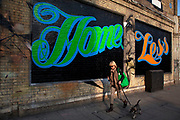 "Street art by Ben Eine spells the phrase 'Home Sweet Home Less' in the East End of London is an ever changing visual enigma, as the artworks constantly change, as councils clean some walls or new works go up in place of others. While some consider this vandalism or graffiti, these artworks are very popular among local people and visitors alike, as a sense of poignancy remains in the work, many of which have subtle messages. Ben Eine is best known for the vibrant typographical letters that have popped up all over East London over the past half of the decade. These letters can appear on their own on shop shutters or can spell whole words across East London walls like ""Scary"", ""Exciting"", ""Vandalism"", ""Change"" and ""Calculate""."
