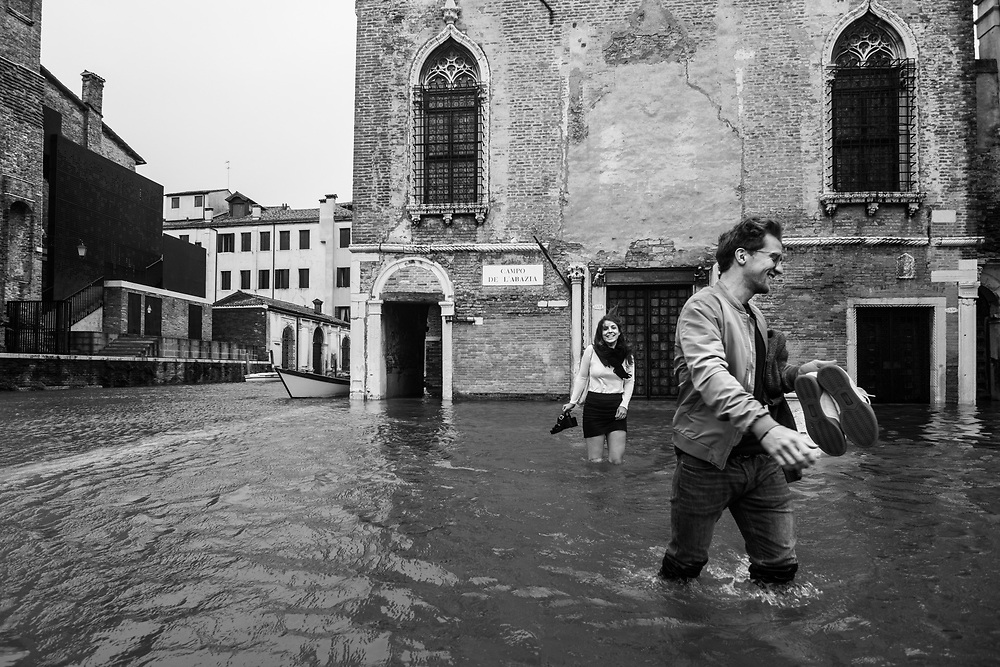 Venice, Italy. 29 October, 2018. A boy and his girlfriend walk in a flooded small square during the high tide on October 29, 2018, in Venice, Italy. This is a selection of pictures of different areas of Venice that the press has not covered, were resident live and every year they have to struggle with the high tide. Due to the exceptional level of the 'acqua alta' or 'High Tide' that reached 156 cm today, Venetian schools and hospitals were closed by the authorities, and citizens were advised against leaving their homes. This level of High Tide has been reached in 1979. © Simone Padovani / Awakening / Alamy Live News