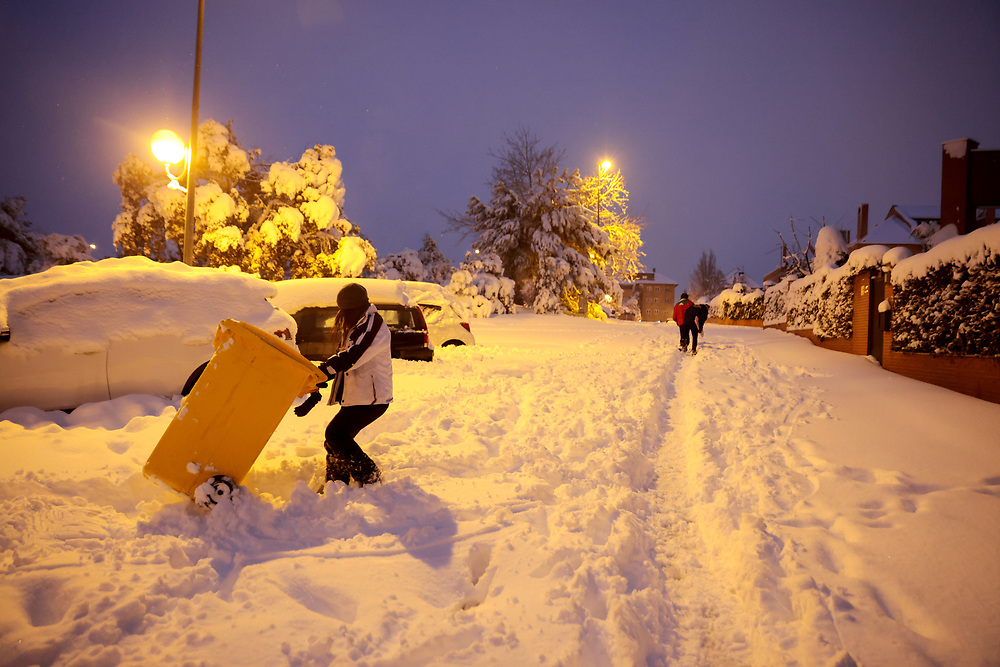 MADRID, SPAIN - JANUARY 9: A young woman pulls a trash container outside her home on a street covered in snow in a residential area as storm Filomena hits the city on January 9, 2021, in Majadahonda, Madrid, Spain.