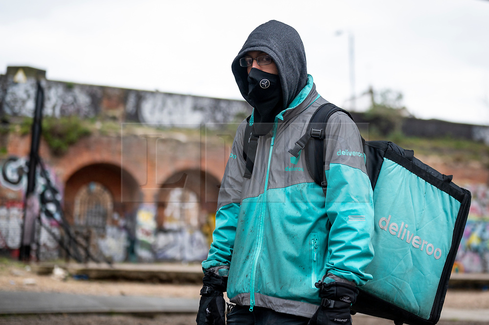 © Licensed to London News Pictures. 07/04/2021. LONDON, UK.  A Deliveroo rider on strike staging a protest outside Shoreditch station against the company demanding improvements to pay and conditions in terms of minimum wage, holidays and sick leave.  The strike comes on the same day that the company's shares are publicly traded for the first time following its initial public offering (IPO) on 31 March, where shares fell by 25% after failing to receive support by institutional investors who cited concerns about the company's policy on workers' rights.  Photo credit: Stephen Chung/LNP