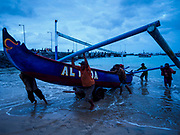 03 AUGUST 2017 - KUTA, BALI, INDONESIA:  Men push their outrigger fishing canoes up onto Jimbrana Beach in Kuta after a night of fishing on the Indian Ocean. The beach is close to the airport and a short drive from other beaches in southeast Bali. Jimbrana was originally a fishing village with a busy local market. About 25 years ago, developers started building restaurants and hotels along the beach and land prices are rising. The new emphasis on tourism is changing the nature of the area but the fishermen are still busy very early in the morning.    PHOTO BY JACK KURTZ