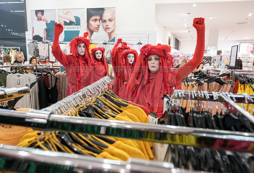"""© Licensed to London News Pictures. 01/06/2019. Bristol, UK. Extinction Rebellion's """"Redwatch"""" protest inside Primark at Bristol's Broadmead shopping centre. Campaigners from Extinction Rebellion are carrying out a five-hour protest which will include everything from a 'pop-up' catwalk to blocking the city centre traffic. The protest targets Bristol's fashion and clothes stores with people urged to not buy any new items of clothing for the next year. There will also be a 'pop-up catwalk', where designers will be showing off their work to demonstrate the needed shift away from fast fashion towards a fairer, safer, cleaner, more transparent fashion industry. People are encouraged to repair, re-use, alter, upcycle and recycle clothes in a year-long boycott aiming to economically disrupt the fashion and textile industry demanding that it drastically changes the way it currently exploits people and planet for profit. The protest is part of a series of disruptive activities planned by Extinction Rebellion to highlight the fashion industry's contribution to climate change, biodiversity loss and environmental pollution. Photo credit: Simon Chapman/LNP."""