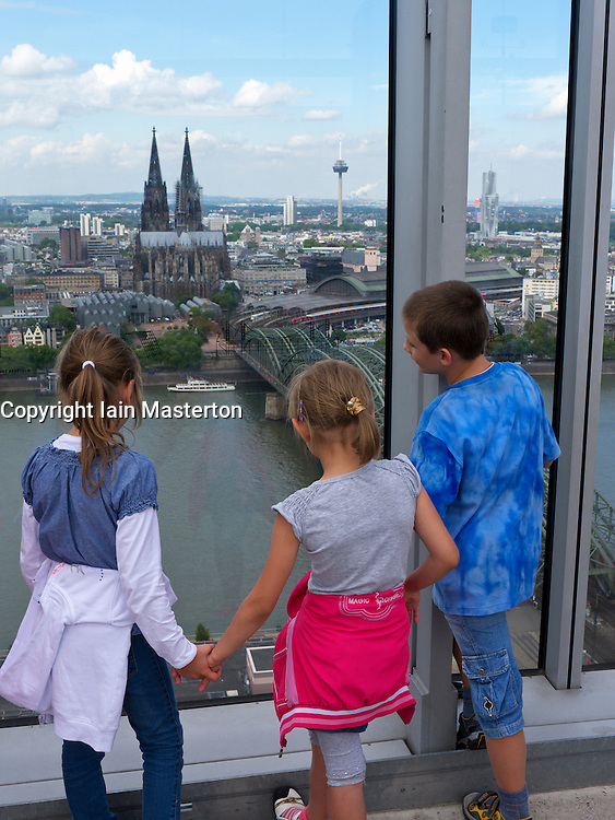 Children looking at skyline view of Cologne from observation platform in high rise building
