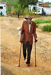 An Angolan man who lost his leg to a landmine walks several miles on crutches from a camp for internally displaced people to get food in the town of Huambo in Angola, Friday March 3, 2000. Angola's brutal 26 year-civil has displaced around two million people - about a sixth of the population - and 200 die each day according to United Nations estimates. .(Photo by Ami Vitale)