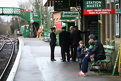 © Licensed to London News Pictures. 07/03/2014. Hampshire, UK. A man and two boys waiting for the next train at Alresford Station today, 7th March 2014, which is the first day of the 'spring steam gala' on the Watercress Line. The railway line, operated by Mid Hants Railway Ltd, passes between Alresford and Alton in Hampshire. The line is named after its use in the past for transporting freshly cut watercress from the beds surrounding Alresford to London. Photo credit : Rob Arnold/LNP