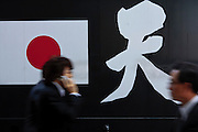 Japanese office workers or salarymen walk past a black sound truck  or gaisensha belonging to the Uyoku Dantai or Japanese right wing nationalists in Shimbashi, Tokyo, Japan Wednesday, April 8th 2009