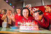 27 JULY 2013 - BANGKOK, THAILAND:  TIDA TAVONSETH, (center left), the president of the United Front for Democracy against Dictatorship, popularly known as the Red Shirts, blows out the candles on the birthday cake for Thaksin Shinawatra at the party for Thaksin. The Red Shirts celebrated former Prime Minister Thaksin Shinawatra's 64th birthday with a party at Phibun Prachasan School in Bangkok. They had a Buddhist Merit Making Ceremony, dinner, cake and entertainment. Most of the Red Shirt political elite traveled to Hong Kong for a party with Thaksin. Thaksin, the former Prime Minister, was deposed by a coup in 2006 and subsequently convicted of corruption related crimes. He went into exile rather than go to jail but remains very popular in rural parts of Thailand. His sister, Yingluck Shinawatra is the current Prime Minister and was elected based on her brother's recommendation.    PHOTO BY JACK KURTZ