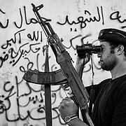Libye, Syrte le 21-09-11 Sur la ligne de front de Syrte, bastion pro Kadhafi, L'OTAN a procédé à plusieurs frappes sur des points stratégiques demandant aux combattants pro CNT de ne pas intervenir. Un rebelle surveille la progression des troupes loyalistes sur la première ligne de front.