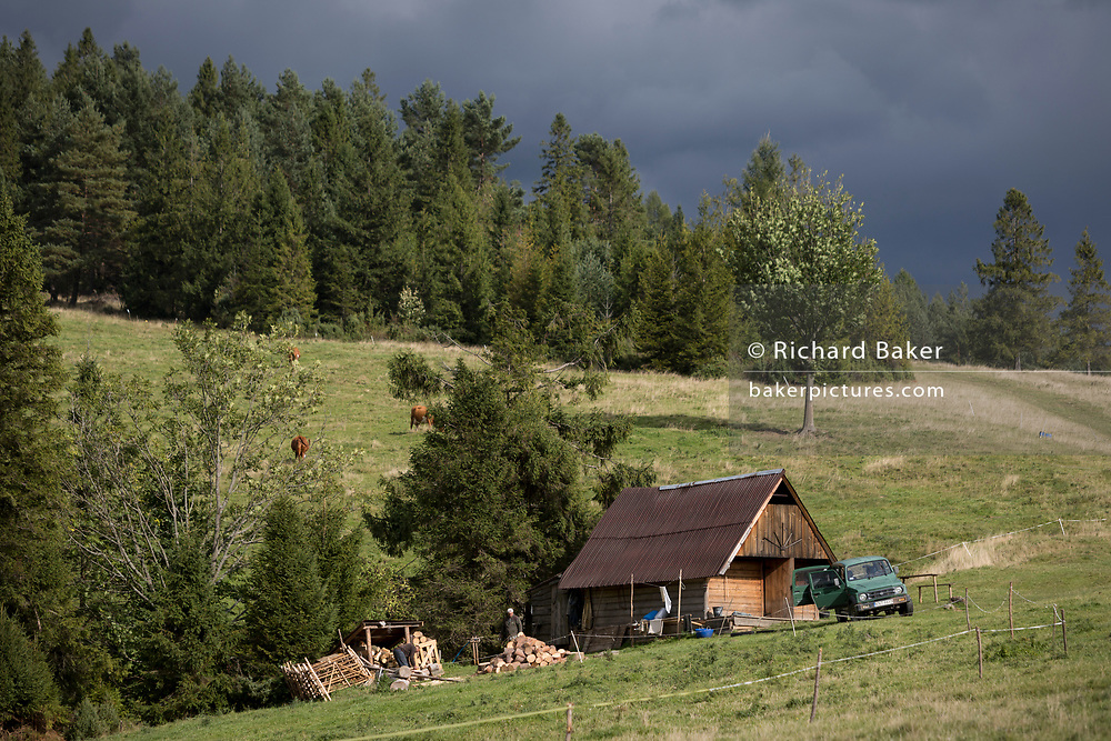 Agricultural workers chop wood in front of a traditional Polish shepherd's hut on the hillside, on 20th September 2019, Biala Woda, Jaworki, near Szczawnica, Malopolska, Poland.