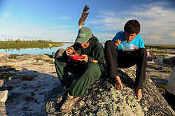 "Miles Catholique, 14, left and Brendan Felix Head, 14, eat at a campsite in the Thelon, the largest and most remote game sanctuary in North America, which almost no one has heard of.  For the Akaitcho Dene, the Upper Thelon River is ""the place where God began.""  Sparsely populated, today few make it into the Thelon. Distances are simply too far, modern vehicles too expensive and unreliable. For the Dene youth, faced with the pressures of a western world, the ties that bind the people and their way of life to the land are even more tenuous. Every impending mine, road, and dam construction threatens to sever these connections. In July and August, 2011 a group of youth paddled to their ancestral hunting ground and spiritual abode.  this next generation of young leaders will be the ones who will need to speak for the Thelon the loudest. (Photo by Ami Vitale)"