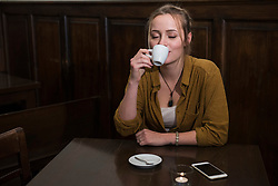 Young woman with eyes closed drinking coffee while mobile kept on table at restaurant