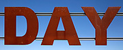Large red rusty capital letters spell the word DAY against blue sky background, Alqueva dam, Moura, Portugal