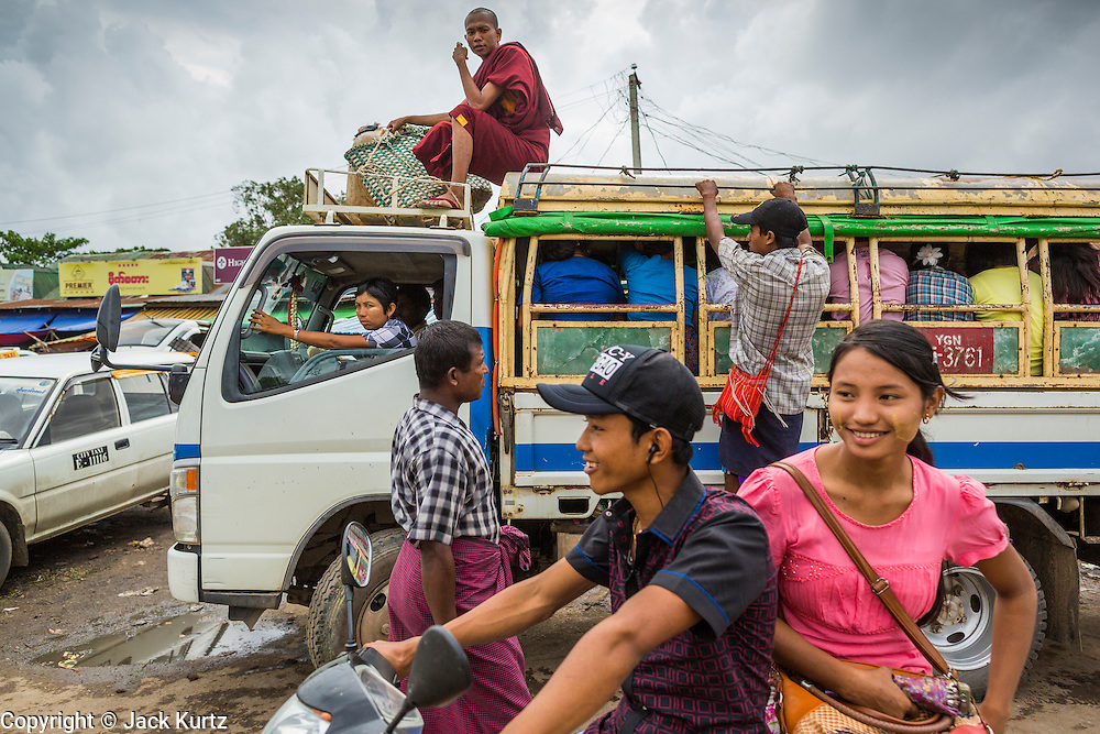 08 JUNE 2014 - YANGON, MYANMAR: A monk rides on top of a minibus back to his temple in Dala opposite Yangon. The ferry to Dala runs continuously through the day between Yangon and Dala. Yangon, Myanmar (Rangoon, Burma). Yangon, with a population of over five million, continues to be the country's largest city and the most important commercial center.      PHOTO BY JACK KURTZ