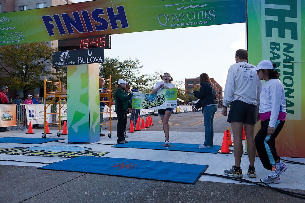 This photo is of the first woman runner at the finish line. The runners begin arriving at the finish line after the shorter races within 15 minutes of the start of the Quad Cities Marathon 2010.