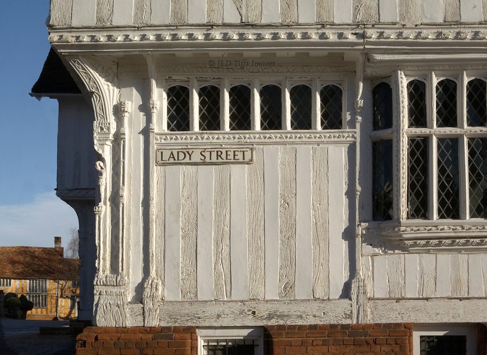 Lavenham townscapes and architecture.  Detail of its Guildhall, now painted white, on the corner of Lady Street.  Fine ornamental detail carved on the corner, uprights, cornice, and window frames