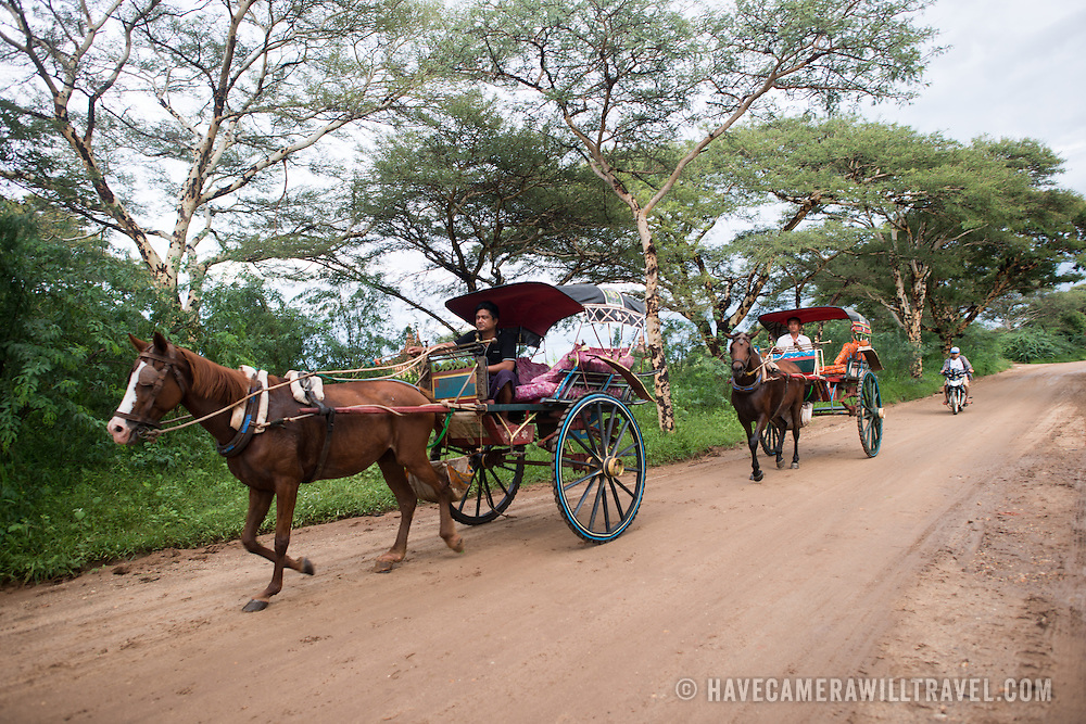 Horse and buggies offering rides to tourists amongst the famous ruins and pagodas of Bagan, Myanmar.