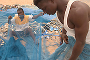 Fishermen repairing fishing nets on the beach at Aflao, Volta region, Eastern Ghana.