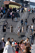 A man carries his bike alongside other pedestrians on the steps at one of the entrances of Westfield at Stratford, on 11th August 2021, in London, England.
