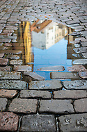 Tallinn, Estonia - July 9, 2015: A rain puddle reflects buildings in a quiet alley in the historic old town of Tallinn, Estonia.