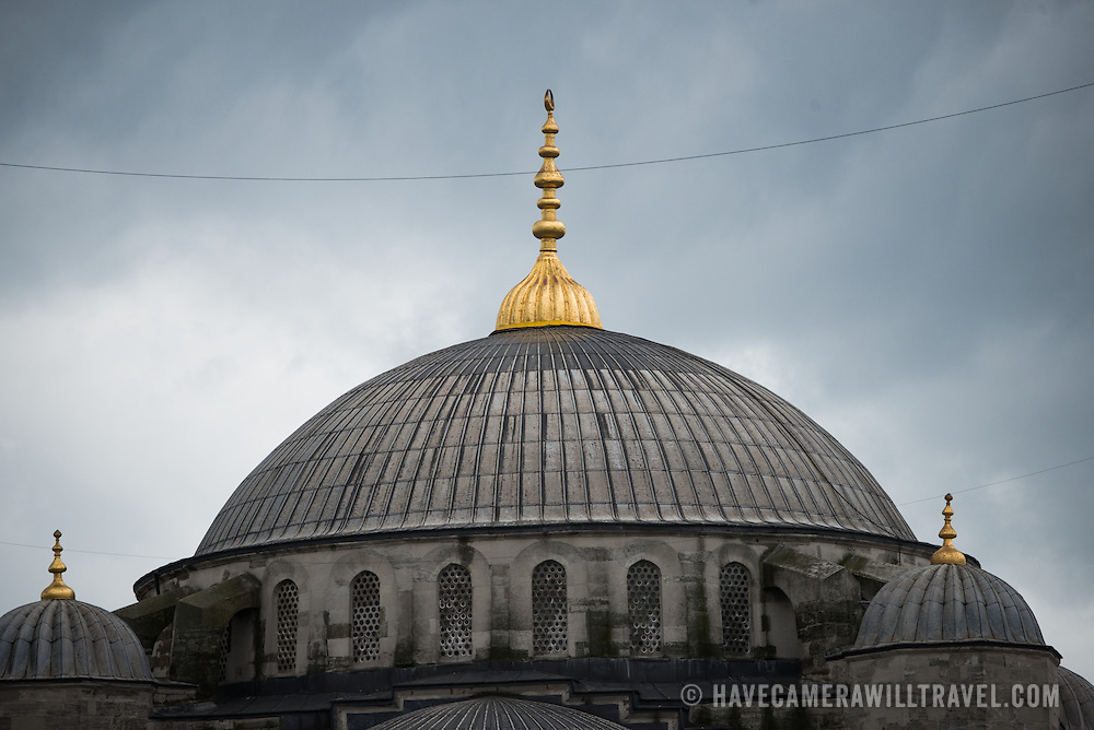 Domes of Istanbul's Blue Mosque against a cloudy sky. While it is widely known as the Blue Mosque for the its interior tiling, the mosque's formal name is Sultan Ahmed Mosque (or Sultan Ahmet Camii in Turkish). It was built from 1609 to 1616 during the rule of Sultan Ahmed I.