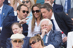 © Licensed to London News Pictures. 12/07/2019. London, UK. Jude Law, Anna Grant and Hugh Grant watch centre court tennis in the royal box on Day 11 of the Wimbledon Tennis Championships 2019 held at the All England Lawn Tennis and Croquet Club. Photo credit: Ray Tang/LNP