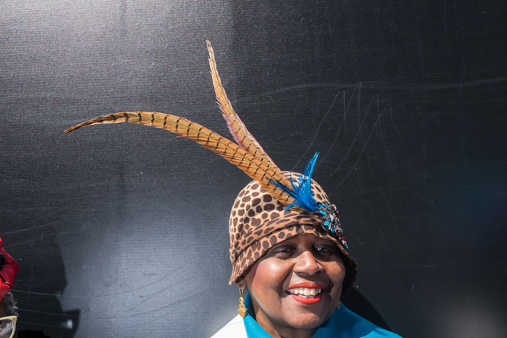 New York, NY, USA-27 March 2016. Milliner Evetta Petty wears one of her hats, decorated in swooping pheasant feathers, and with turquoise accents, on Fifth Avenue in the annual Easter Bonnet Parade and Festival. Ms. Petty, who owns the oldest hat shop in Harlem, was there with a group from the Milliners Guild.
