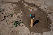 A pipe protrudes from the ground that leads to a buried cistern that holds about 1,000 gallons of water in front of a home in Coyote Canyon Chapter in the Navajo Nation.
