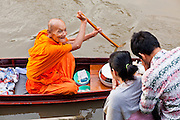 "10 JULY 2011 - AMPHAWA, SAMUT SONGKRAM, THAILAND:   People pray and present their alms to a Buddhist monk on the main canal in Amphawa, Thailand, about 90 minutes south of Bangkok. The Thai countryside south of Bangkok is crisscrossed with canals, some large enough to accommodate small commercial boats and small barges, some barely large enough for a small canoe. People who live near the canals use them for everything from domestic water to transportation and fishing. Some, like the canals in Amphawa and nearby Damnoensaduak (also spelled Damnoen Saduak) are also relatively famous for their ""floating markets"" where vendors set up their canoes and boats as floating shops.      PHOTO BY JACK KURTZ"