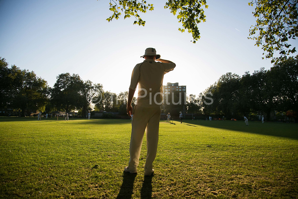 A cricket player stands in the sun watching the game unfold in London Fields Park in East London, United Kingdom,Sept 11 2016. The park has got its own cricket team and matches are held regularly on the pitch in park.