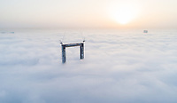 Aerial view of the frame building under construction crossing the clouds of Dubai, U.A.E.