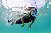 A young child snorkels off the coast of Hawaii.